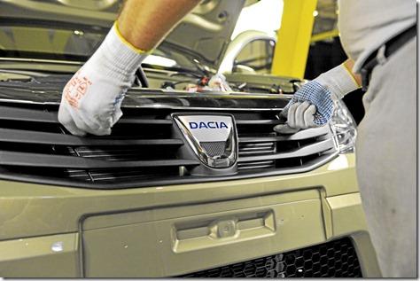 Mise en place du bouclier avant avec le logo Dacia.Gand d'un ouvrier
